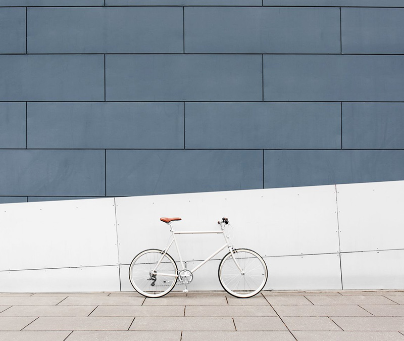 trendy white bike leaning against wall